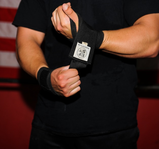 U.S. Air Force Staff Sgt. David Labrie, 612th Support Squadron lead meteorologist and powerlifter, wraps his wrists before lifting during a training session at a crossfit gym in Tucson, Ariz., Aug. 7, 2014. Labrie wraps his wrist to help strengthen them as well as give him the appropriate range of motion during each lift. (U.S. Air Force photo by Airman 1st Class Sivan Veazie/Released)