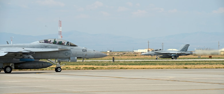 A F-18F Super Hornet, assigned to VFA 154 Naval Air Station Lemoore, Calif., taxis on the runway Aug. 5, 2014, at Mountain Home Air Force Base, Idaho, while another F-18F Super Hornet takes off behind it. The VFA 154 aircrews have been acting as Red Force during combat training scenarios against 389th Fighter Squadron [Blue Force] aircraft while here. (U.S. Air Force photo by Senior Airman Benjamin Sutton/Released)