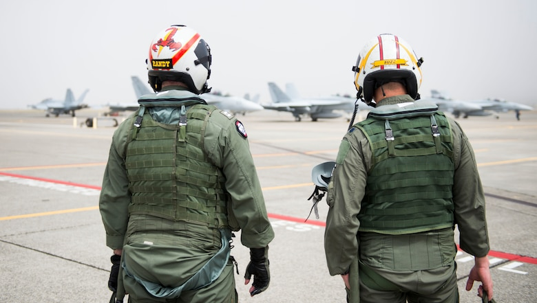 U.S. Air Force Lt. Col. Don Keen, 390th Electronic Combat Squadron commander, and Lt. Randy Scoby, VAQ-129 EA-18G Growler electronic warfare officer, talk before a flight on the EA-18G Growler at Naval Air Station Whidbey Island, Wash., August 7, 2014. The missions of the Growler will be strategic resources for Air Force aircrew and combat forces. (U.S. Air Force photo by Airman 1st Class Malissa Lott/RELEASED)