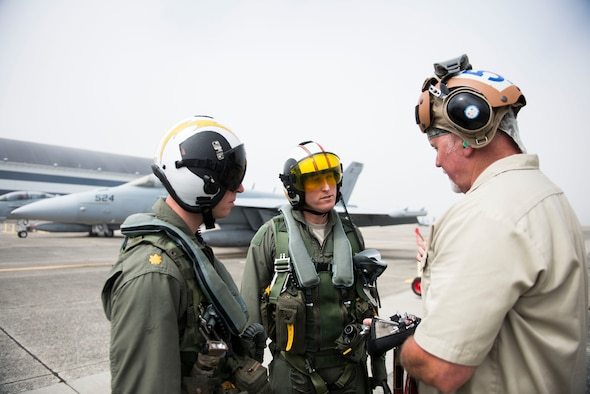 U.S. Air Force Lt. Col. Don Keen, 390th Electronic Combat Squadron commander, and Lt. Cmdr. Kerry Hicks, VAQ-129 EA-18G Growler pilot, receives a briefing before a flight in the EA-18G Growler at Naval Air Station Whidbey Island, Wash., August 7, 2014. Electronic attack missions are extremely complex and vital to providing cover for friendly aircraft during joint-combat operations. (U.S. Air Force photo by Airman 1st Class Malissa Lott/RELEASED)