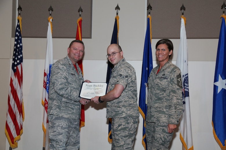 """Brig. Gen. Samuel """"Bo"""" Mahaney, Air Reserve Personnel Center commander, and Chief Master Sgt. Ruthe Flores, ARPC command chief, present the Honor Guard award to Airman 1st Class George Edmund, 566th Intelligence Squadron, during the Team Buckley quarterly awards ceremony Aug. 8 on Buckley Air Force Base, Colo. (U.S. Air Force photo/Quinn Jacobson)"""