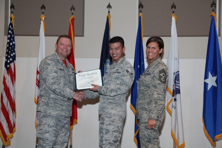 """Brig. Gen. Samuel """"Bo"""" Mahaney, Air Reserve Personnel Center commander, and Chief Master Sgt. Ruthe Flores, ARPC command chief, present the Dormitory award to Airman 1st Class Rajah Pangan, 460th Space Wing, during the Team Buckley quarterly awards ceremony Aug. 8 on Buckley Air Force Base, Colo. (U.S. Air Force photo/Quinn Jacobson)"""