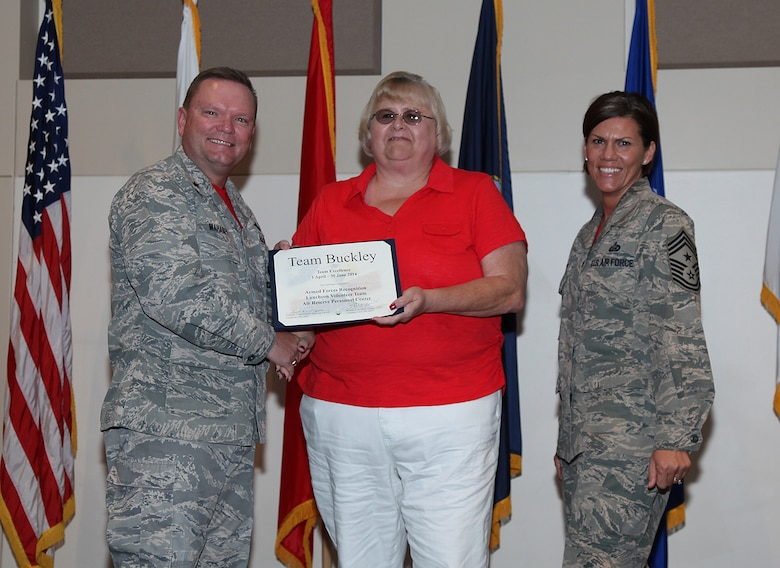 """Brig. Gen. Samuel """"Bo"""" Mahaney, Air Reserve Personnel Center commander, and Chief Master Sgt. Ruthe Flores, ARPC command chief, present the Team Excellence Award to Cindy Dewey, ARPC Armed Forces Recognition Luncheon Volunteer Team, during the Team Buckley quarterly awards ceremony Aug. 8 on Buckley Air Force Base, Colo. (U.S. Air Force photo/Quinn Jacobson)"""
