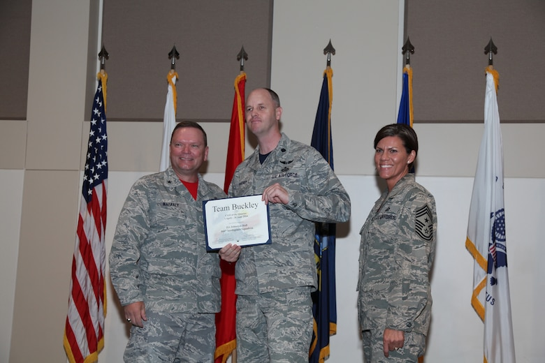 """Brig. Gen. Samuel """"Bo"""" Mahaney, Air Reserve Personnel Center commander, and Chief Master Sgt. Ruthe Flores, ARPC command chief, present the Company Grade Officer award to 1st Lt. Johnston Hall, 566th Intelligence Squadron, during the Team Buckley quarterly awards ceremony Aug. 8 on Buckley Air Force Base, Colo. (U.S. Air Force photo/Quinn Jacobson)"""