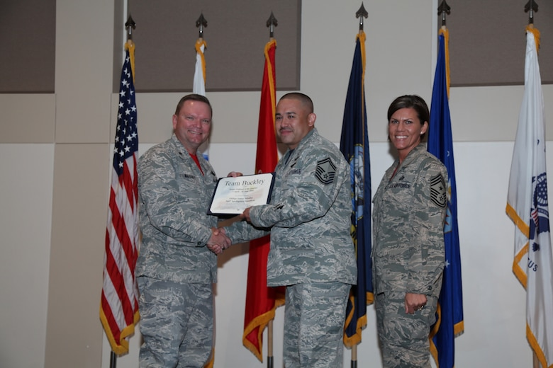 """Brig. Gen. Samuel """"Bo"""" Mahaney, Air Reserve Personnel Center commander, and Chief Master Sgt. Ruthe Flores, ARPC command chief, present the Senior Enlisted award to Senior Master Sgt. James Seballas, 566th Intelligence Squadron, during the Team Buckley quarterly awards ceremony Aug. 8 on Buckley Air Force Base, Colo. (U.S. Air Force photo/Quinn Jacobson)"""