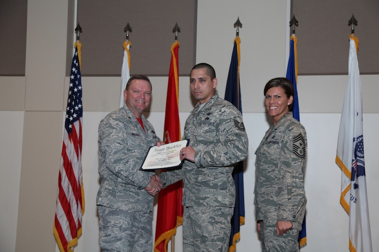 """Brig. Gen. Samuel """"Bo"""" Mahaney, Air Reserve Personnel Center commander, and Chief Master Sgt. Ruthe Flores, ARPC command chief, present the Middle Enlisted award to Tech. Sgt. Kristopher Kainoa, 460th Space Wing during the Team Buckley quarterly awards ceremony Aug. 8 on Buckley Air Force Base, Colo. (U.S. Air Force photo/Quinn Jacobson)"""
