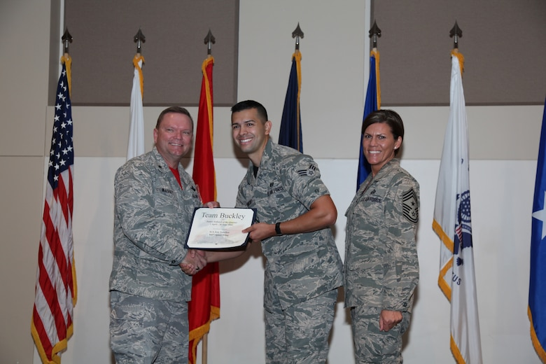 """Brig. Gen. Samuel """"Bo"""" Mahaney, Air Reserve Personnel Center commander, and Chief Master Sgt. Ruthe Flores, ARPC command chief, present the Junior Enlisted award to Senior Airman Jose Sanchez, 460th Space Wing, during the Team Buckley quarterly awards ceremony Aug. 8 on Buckley Air Force Base, Colo. (U.S. Air Force photo/Quinn Jacobson)"""