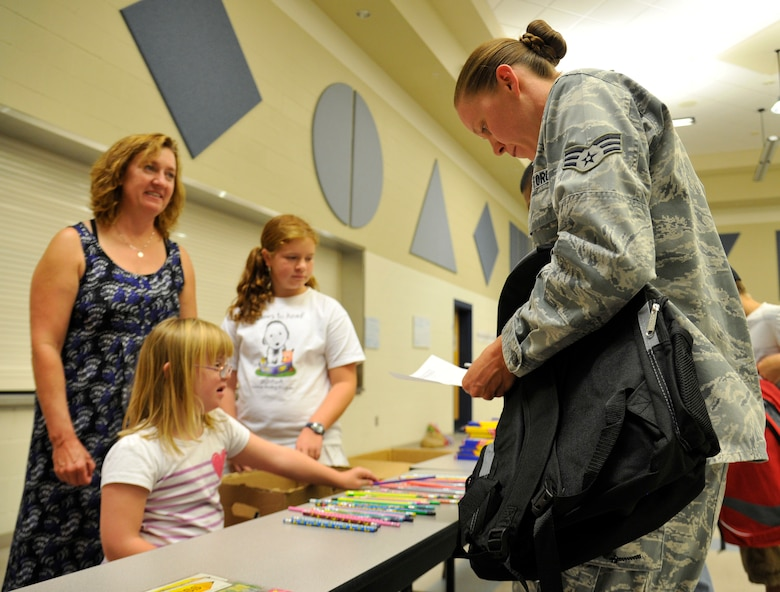 Marlee McDaniel hands out school supplies to Senior Airman Laura Clay during Operation Homefront's Back-to-School Brigade in the Michael Anderson Elementary School gymnasium at Fairchild Air Force Base, Washington, Aug. 7, 2014. Operation Homefront was formed in 2002 and since then has used 128 million dollars to help military families. Clay is a 92nd Logistics Readiness Squadron aircraft parts store journeyman. (U.S. Air Force photo by Senior Airman Ryan Zeski/Released)