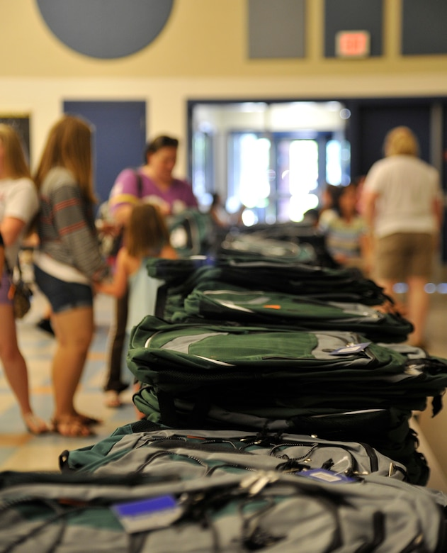 Family members of Team Fairchild pick out book bags during Operation Homefront's Back-to-School Brigade in the Michael Anderson Elementary School gymnasium at Fairchild Air Force Base, Washington, Aug. 7, 2014. Operation Homefront was formed in 2002 and since then has used 128 million dollars to help military families. (U.S. Air Force photo by Senior Airman Ryan Zeski/Released)