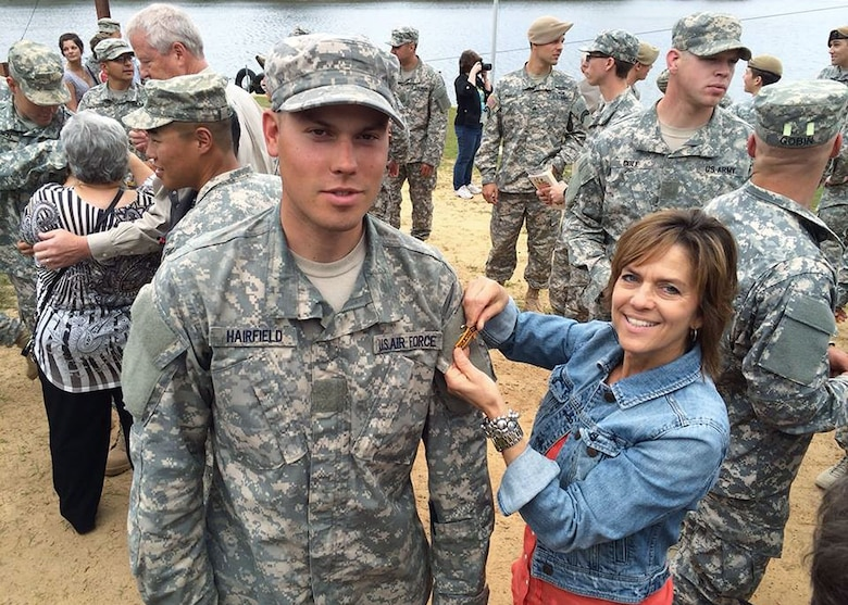Senior Airman Austin Hairfield, 14th Air Support Operations Squadron tactical air control party member, poses as his mother, Melinda Harifield, pins his Ranger tab onto his uniform shortly after graduating from Army Ranger School. (Courtesy photo)