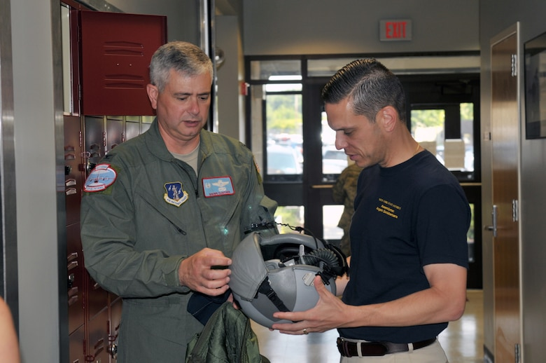 Col. Shawn Clouthier, 109th Airlift Wing commander, shows Assemblyman Angelo Santabarbara, 111th District, a pilot's helmet during a tour at Stratton Air National Guard Base, Scotia, New York, on Aug. 9, 2014. Santabarbara learned about the 109th's unique mission and also got to see the inside of an LC-130 Skibird. (U.S. Air National Guard photo by Staff Sgt. Benjamin German/Released)