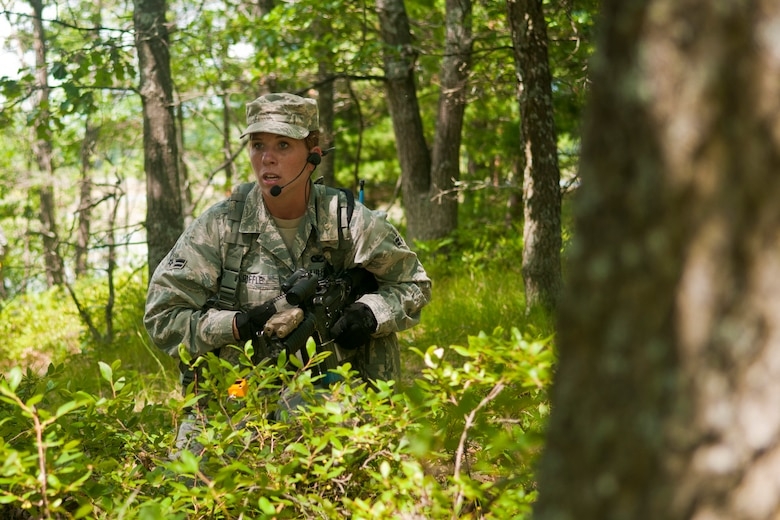 U.S. Air Force Airman 1st Class Heidi Riffle, 121st Air Refueling Wing Security Forces Squadron, Rickenbacker Air National Guard Base, Ohio, maneuvers through the woods during the SFS annual training at the Alpena Combat Readiness Training Center, Mich., August 5, 2014. During the training, 121st SFS Airmen received instruction on mission planning, land navigation, building entry, casualty evacuation, and how to shoot, move and communicate. (U.S. Air National Guard photo by Airman 1st Class Wendy Kuhn/Released)