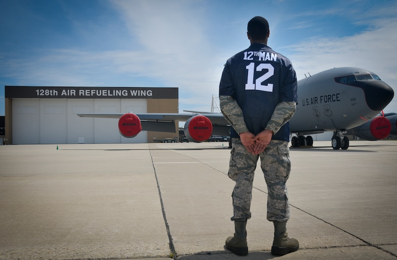 An Airman with the 128th Air Refueling Wing displays the Force Support Squadron 12th Man award jersey in front of a KC-135R Stratotanker here on August 10, 2014. Service members with the 128 ARW FSS created the FSS 12th Man award to recognize those who are reaching above and beyond for their fellow airmen. (U.S. Air National Guard photo by Airman Morgan Lipinski/Released)