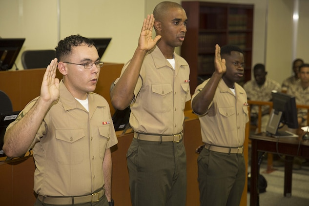 From left to right, Lance Cpl. Jorge Meza, Lance Cpl. Shaqueal Coote, and Pfc. Kervens Beauplan recite the Oath of Allegiance aboard Marine Corps Air Station Iwakuni, Japan, July 17, 2014. Before the oath, the Marines were interviewed about U. S. history by Walter Haith, the field office director of U.S. Citizenship and Immigration Services Attaché, Republic of Korea and Japan.