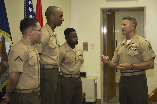 Sgt. Maj. Keith Massi, Station sergeant major, talks to (from left to right) Lance Cpls. Jorge Meza and Shaqueal Coote and Pfc. Kervens Beauplan after their naturalization ceremony aboard Marine Corps Air Station Iwakuni, Japan, July 17, 2014. The naturalization ceremony was held to award the Marines their U.S. citizenship.