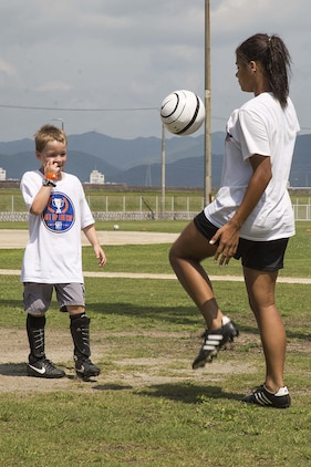 Kalaila Holt, a member of the Southern California Seahorse Soccer Club, practices juggling techniques with a Seahorse soccer camp participant at Penny Lake fields aboard Marine Corps Air Station Iwakuni, Japan, July 23, 2014. The Seahorses are a motivational, religious soccer team who carry out numerous after-school clinics, camps, international tours and many other outreach programs throughout Asia and the U.S. west coast.