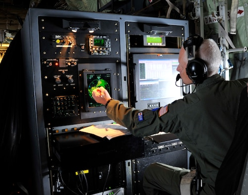 "Lt. Col. Jon Talbot, 53rd Weather Reconnaissance Squadron aerial reconnaissance weather officer, points to the eye of Hurricane Julio during a hurricane flight off the coast of Hawaii Aug. 9, 2014. The 53rd WRS ""Hurricane Hunters"" aircrew and 403rd Wing maintenance personnel deployed to Joint Base Pearl Harbor-Hickam, Hawaii, to fly storm missions into Hurricanes Iselle and Julio. The ""Hurricane Hunters"" fly storm missions in both the Atlantic and Pacific Oceans during the hurricane season June 1 to Nov. 30 yearly. (U.S. Air Force photo by Master Sgt. Jessica Kendziorek)"