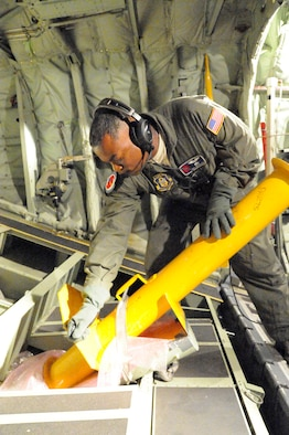 "Master Sgt. Troy Bickham. 53rd Weather Reconnaissance Squadron loadmaster and dropsonde operator, pulls the handle on the launch adapter to release an ABXT buoy used by the U.S. Navy to collect salinity and water temperature during a flight through Hurricane Iselle off the coast of Hawaii Aug 7.   The 53rd WRS ""Hurricane Hunters"" aircrew and 403rd Wing maintenance personnel deployed to Hickham Air Force Base, Hawaii to fly storm missions into Hurricanes Iselle and Julio.  The ""Hurricane Hunters"" fly storm missions in both the Atlantic and Pacific Oceans during the hurricane season which offically starts June 1 and ends Nov. 30 yearly. (U.S. Air Force photo by Master Sgt. Jessica Kendziorek)"