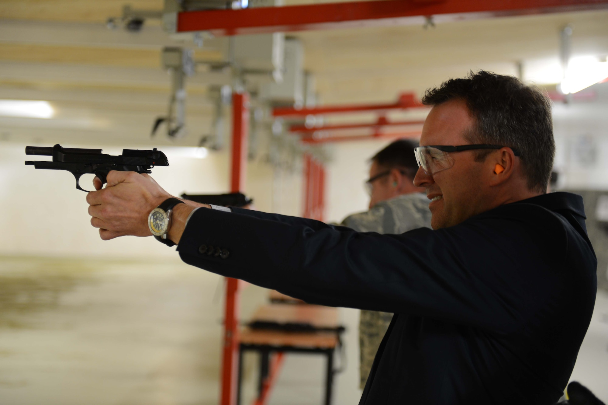 Under Secretary of the Air Force Eric Fanning fires a pistol at the combat arms training building during a base familiarization visit Aug. 5, 2014, on Spangdahlem Air Base, Germany. Fanning spoke with Airmen at locations across the base to hear how they directly contribute to operations and readiness. (U.S. Air Force photo/Senior Airman Gustavo Castillo)