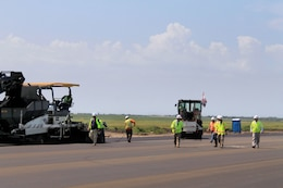 Asphalt paving crews at Minot Air Force Base, N.D., are using a three-wheeled roller for initial asphalt compaction providing tight joint compaction between the concrete and asphalt.