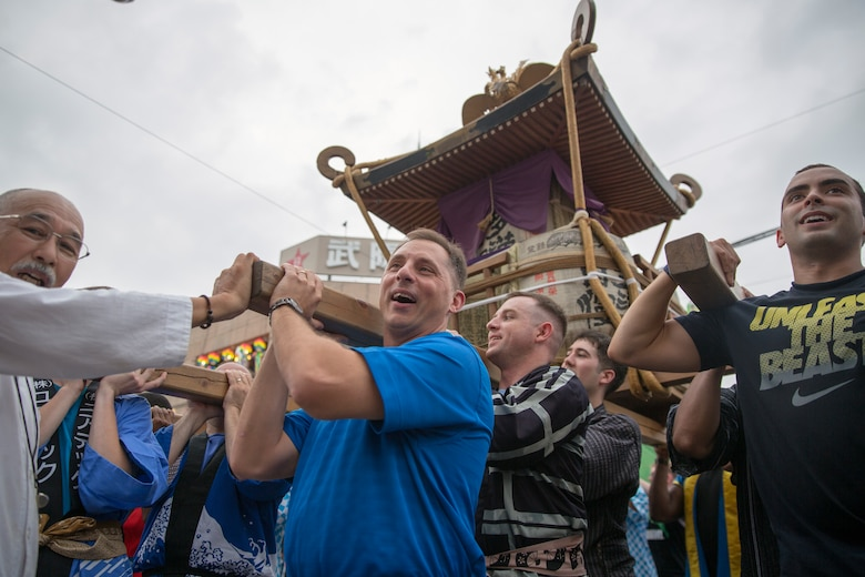 Col. Scott Maskery, 374th Mission Support Group commander, carries a mikoshi shrine with airmen in front of Fussa City Hall, Fussa city, Japan, Aug. 8, 2014. Multiple shrines were carried from the Fussa shinmei-sha, shinto shrine, to City Hall during the 64th annual Fussa Tanabata Festival. (U.S. Air Force photo by Osakabe Yasuo/Released)
