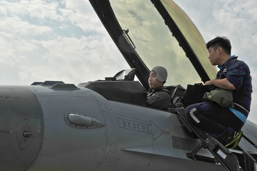 Republic of Korea air force Tech. Sgt. Won il Lee, 161st Squadron crew chief, talks with ROKAF Capt. Bon hyuk Koo, 161st SQ pilot, before a flight during the Buddy Wing 14-6 exchange program on Osan Air Base, Republic of Korea, July 31, 2014. The program is intended to enhance the partnership between the United States and ROKAF. (U.S. Air Force photo by Senior Airman Matthew Lancaster)