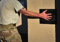 A member from 26th Special Tactics Squadron places his hand over a plaque honoring another fallen Special Forces troop before entering the DZ Pool for the next component of a Monster Mash Aug. 6, 2014 at Cannon Air Force Base, N.M. The Air Commandos participating in the event were memorializing the sacrifices of those who lost their lives aboard Extortion 17. (U.S. Air Force photo/Staff Sgt. Alexxis Pons Abascal)