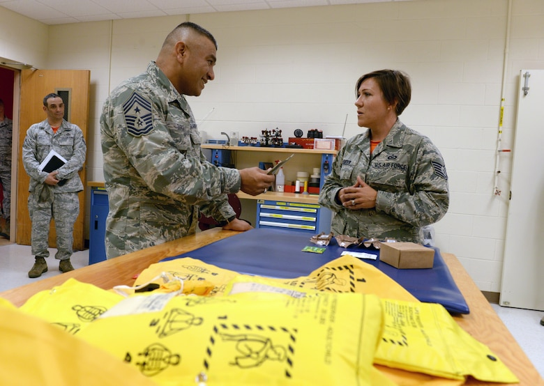 ALTUS AIR FORCE BASE, Okla. – U.S. Air Force Tech. Sgt. Christie Kidder, 97th Operations Support Squadron aircrew flight equipment technician, explains cost-saving initiatives to reduce waste to U.S. Air Force Chief Master Sgt. Gerardo Tapia, command chief of Air Education and Training Command, during Tapia's visit to the 97th Air Mobility Wing Aug. 8, 2014. The squadron developed an initiative to donate expiring non-perishable food to a nearby food bank. (U.S. Air Force photo by Staff Sgt. Nathanael Callon/Released)