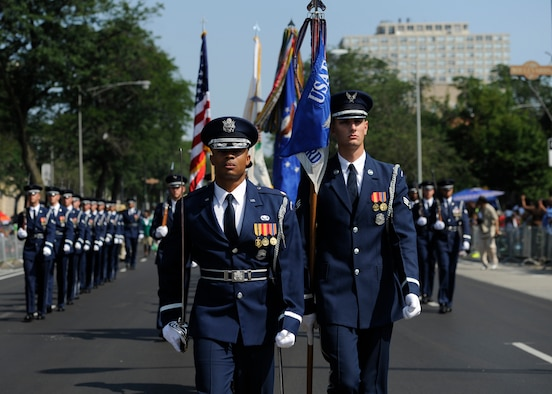 Maj. Scott Belton and Senior Airman Nicholas Priest lead the United States Air Force Color Team and ceremonial guardsmen during the Bud Billiken Parade in Chicago, Il., August 9, 2014.  Belton is the Assistant Director of Operations and Priest is a member of the Color Flight Team within the USAF Honor Guard. (U.S. Air Force photo/ Senior Airman Nesha Humes)