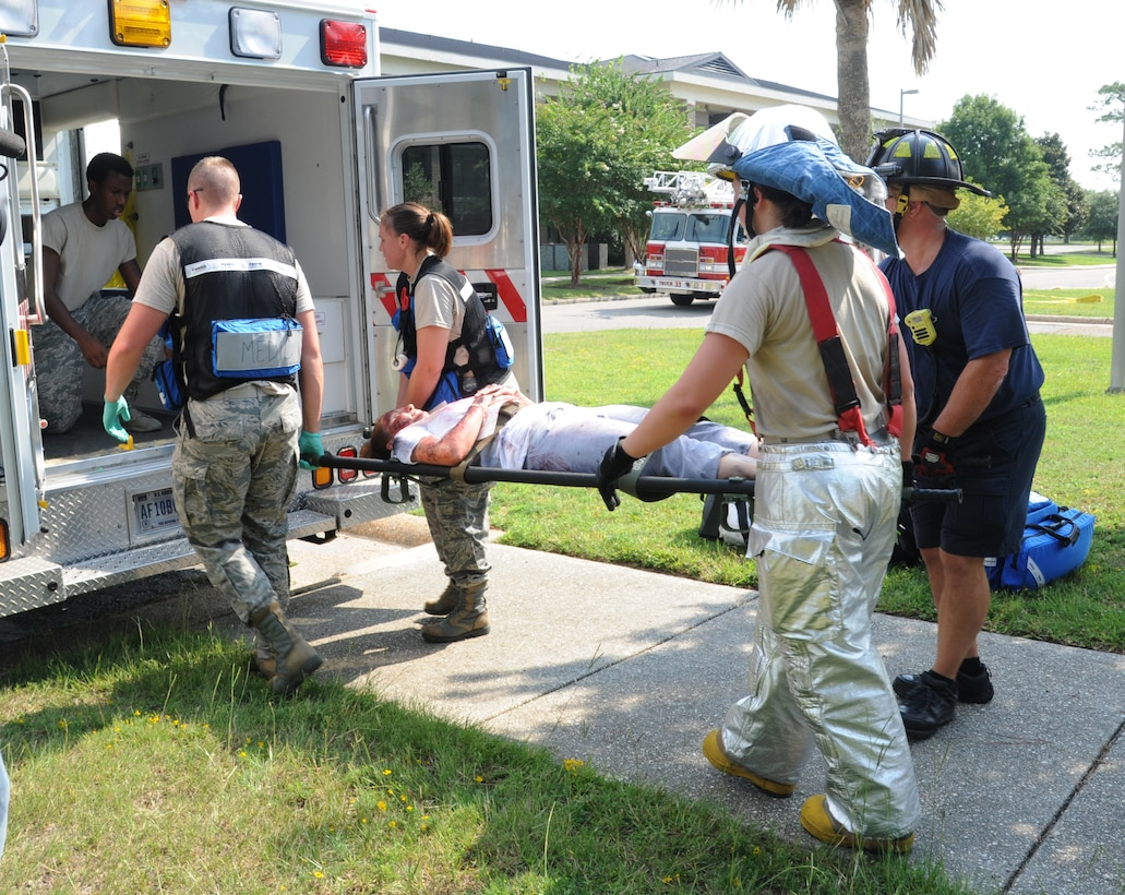 "Members from the Keesler fire department and the 81st Medical Group load a ""victim"" into the back of an ambulance for transportation to the medical center during a major accident response exercise Aug. 7, 2014, at the Locker House at Keesler Air Force Base, Miss. Team Keesler practiced real-world training during the exercise which simulated a gas line explosion that set a building on fire. Due to the extreme temperatures, exercise ""players"" wore minimal fire gear.  (U.S. Air Force photo by Kemberly Groue)"
