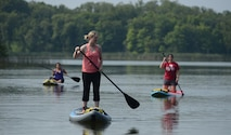 From left to right, Sonia Cazarez, Tami Imlay and Leigh Giglio practice maneuvering paddleboards Aug. 1, 2014, on the calm water of Holbrook Lake, Minn. The women were participated in the retreat for widows of U.S. military members who lost their lives while serving their country. The Holbrook Farms Retreat is hosted by husband and wife Lt. Cols. Matthew and Micaela Brancato, both assigned to the North Dakota Air National Guard's 119th Wing. (U.S. Air Force photo/Senior Master Sgt. David H. Lipp)