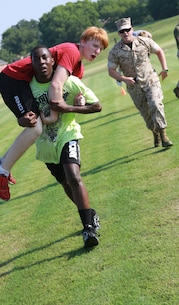 (Right) U.S. Marine Corps Staff Sgt. Isaac C. Acosta, Staff Non Commissioned Officer In Charge, Recruiting Sub Station Denton, encourages an Ardmore High School football player conducting a fireman's carry on a teammate at Ardmore High School, OK, Aug. 4, 2014. The CFT is designed to be functional combat fitness training for deployed Marines. (U.S. Marine Corps photo by Sgt. Alfredo V. Ferrer)