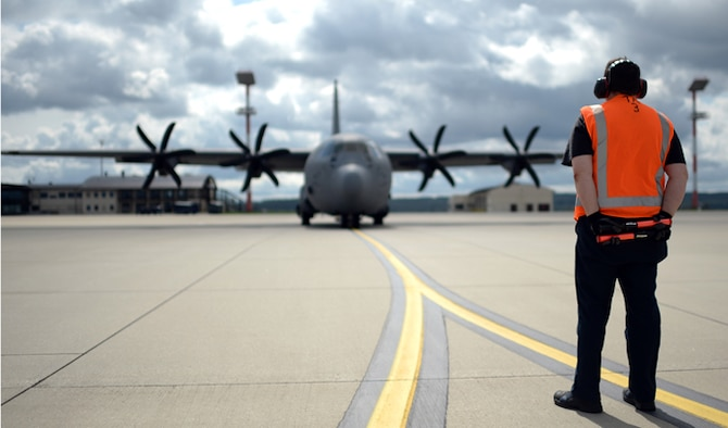 A member of the 726th Air Mobility Squadron waits to marshal a C-130 Hercules on the flightline Aug. 9, 2014, at Spangdahlem Air Base, Germany. Airmen from Spangdahlem AB will be supporting a bilateral training event with the Hellenic air force Aug. 11-23. The training aims to increase the military compatibility between the U.S. and Greece while sustaining capability to secure peace and stability in Europe. (U.S. Air Force photo/Staff Sgt. Daryl Knee)