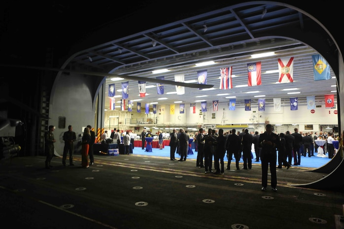 """The lights from the hangar bay of the future amphibious assault ship USS America (LHA 6) shine brightly during a reception at Rio De Janeiro, Brazil, Aug. 7, 2014. The reception was hosted by the Sailors and Marines of America and Special Purpose Marine Air Ground Task Force South for Brazilian diplomats and military officials. The evening of food, music and dancing concluded with speeches from Rear Adm. Frank L. Ponds, commander of Expeditionary Strike Group 3 and The Honorable Liliana Ayalde, U.S. Ambassador to Brazil. America is currently on her maiden transit, """"America Visits the Americas"""". The transit is a clear example of our Nation's commitment to our regional partners and allies, demonstrating the Navy-Marine Corps integration in action. (U.S. Marine Corps photo by 1st Lt. Joshua Pena/Released)"""