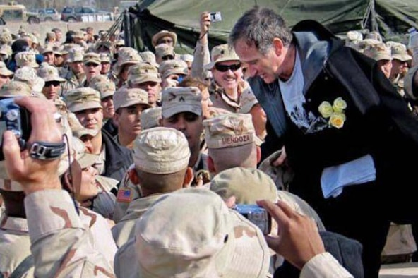 Robin Williams with troops gathered at the Camp Liberty Post Exchange in Baghdad during a USO tour, Dec. 14, 2004. DoD file photo by U.S. Army Sgt. Dan Purcell)