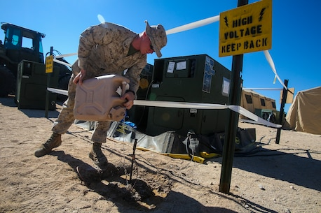 Lance Cpl. Elijah Bingman, an electrician generator operator with 1st Brigade Headquarters Group, Engineers, 1st Marine Expeditionary Brigade from Joplin, Mo., waters the grounding area of a MEP-1060 Generator Set, during Large Scale Exercise 2014 aboard Marine Corps Air Ground Combat Center Twentynine Palms, Calif., Aug. 6, 2014. LSE-14 is a bilateral training exercise being conducted by 1st MEB to build U.S. and Canadian forces' joint capabilities through live, simulated, and constructive military training activities from Aug. 8-14.