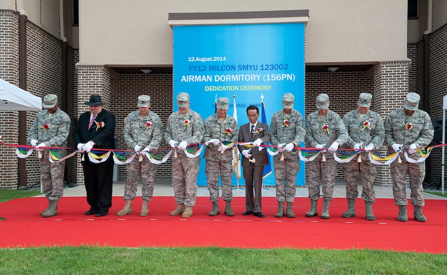 Osan Air Base leadership and Mr. Kwak Sun Ki, Seohee Construction Company president, cut a ribbon during the opening of dormitory 1459 at Osan AB, Republic of Korea, Aug. 12, 2014. The new dormitory will house 156 permanently stationed personnel at Osan AB. The dormitory living areas consist of four person suites, lounge, restrooms in each dorm room, public restrooms, bulk storage, and mechanical rooms.