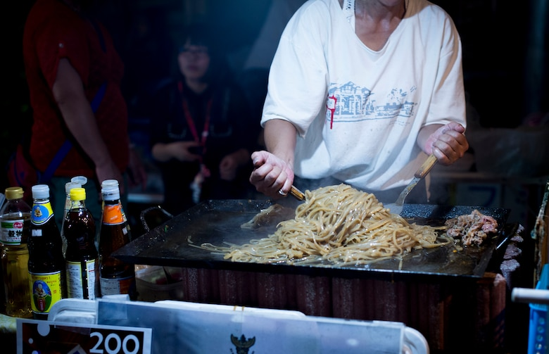 A street vendor cooks noodles at the Fussa Tanabata Festival in Fussa City, Japan, Aug. 8, 2013. Vendors featuring a variety of foods lined the streets for festival participants to enjoy.  (U.S. Air Force photo by Airman 1st Class Meagan Schutter/Released)
