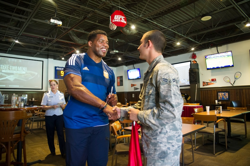 Heisman Trophy winner and former NFL star Herschel Walker meets with Airman 1st Class Casey Cooper, 628th Civil Engineer Squadron, during a meet and greet/autograph session at Rookies in the Charleston Club, Aug. 6, 2014, at Joint Base Charleston, S.C. Walker visited the base to share his story about growing up in Georgia, playing professional football and how he sought help from mental health professionals for his struggles with dissociative identity disorder. Walker spoke and met Sailors and Airmen at both the Weapons Station and Air Base where he met with service members and their families and signed autographs. Walker played college football at the University of Georgia and spent 14 years in the NFL. (U.S. Air Force photo/Staff Sgt. William O'Brien)
