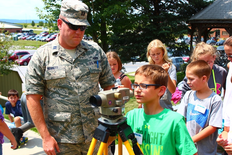 Capt. Blake Bennett, the 167th environmental manager, shows STARBASE Kids campers how to check ground elevation and slope using a level gun, Wednesday, July 30 at the 167th Airlift Wing in Martinsburg, W.Va. (Air National Guard photo by Senior Airman Nathanial Taylor.)