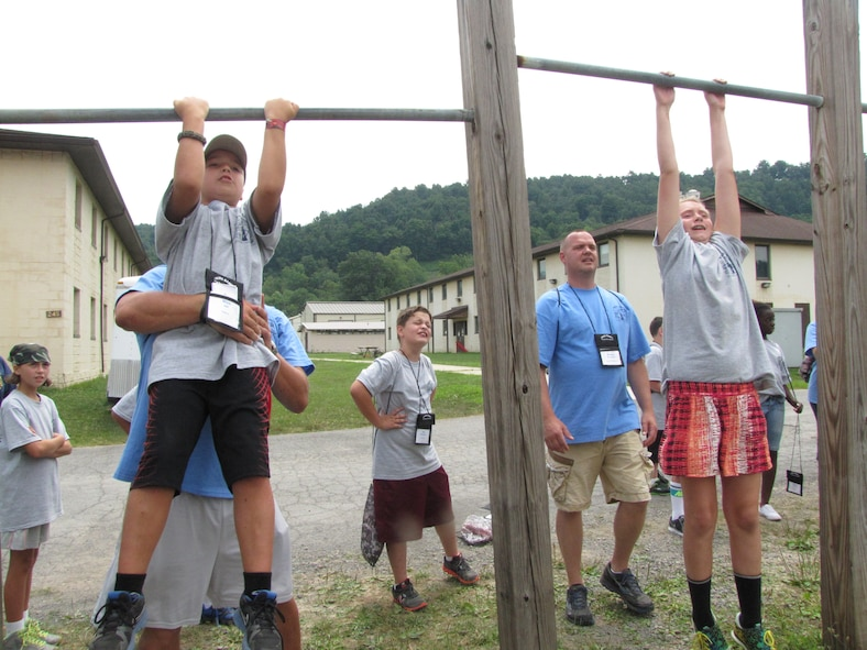 Volunteer counselors help campers perform proper military pull-ups at the 24th Annual West Virginia National Guard Military Kids Kamp. The camp is open to children of West Virginia National Guard members between the ages of 9 and 14. (Air National Guard photo courtesy of Sherry Lewis.)