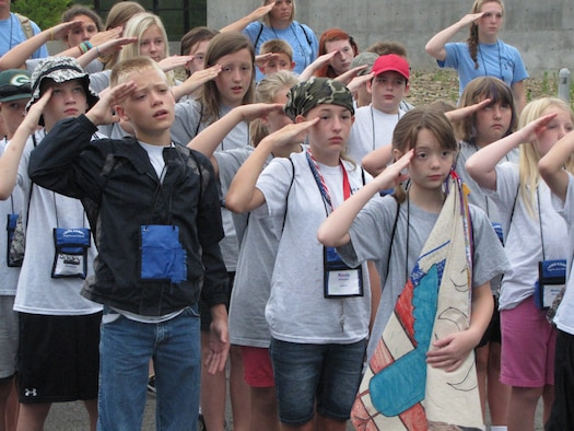 Campers at the West Virginia National Guard Kids Kamp salute the flag during a ceremony at Camp Dawson, W. Va.. The camp, which was held July 12-17, celebrated its 24th year of educating military children. The program began in 1991 as a way to help children of Guardsman, who were deployed in support of Operation Desert Storm, better understand the military. (Air National Guard photo courtesy of Sherry Lewis)