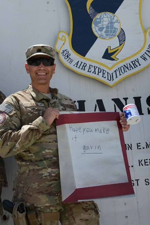 """U.S. Air Force Lt. Col. Roger Bass, NATO Air Training Command-Afghanistan and 438th Air Expeditionary Wing, displays the """"Gavin Fan Club"""" poster at Forward Operating Base Oqab in Kabul, Afghanistan, Aug. 5, 2014. A four-word simple note from a boy named Gavin continues to amuse and inspire deployed servicemembers some 8 months after its arrival. (U.S. Air Force photo/Senior Master Sgt. Mike Hammond)"""