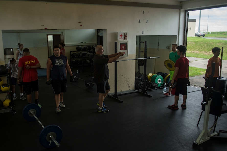 Mike Laue, a Bitburg High School teacher and head coach of the Bitburg High School Barons football team, mentors students during a Bitburg High School summer strength training session Aug. 8, 2014, at Spangdahlem Air Base, Germany. The sessions were open to the entire student body to help students stay in shape during the summer. (U.S. Air Force photo by Senior Airman Rusty Frank/Released)