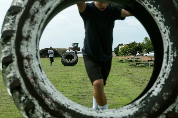 Students from Bitburg High School perform tire rolls during a Bitburg High School summer strength training session Aug. 6, 2014, at Spangdahlem Air Base, Germany. The students work out three days a week to stay in shape for the upcoming sports seasons. (U.S. Air Force photo by Senior Airman Rusty Frank/Released)