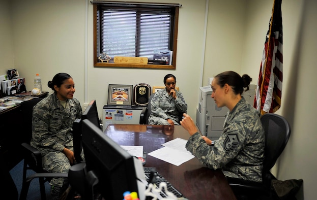 """Tech. Sgt. Alejandra Chavez, 51st Fighter Wing Equal Opportunity NCO in charge, listens to Master Sgt. Jessica McWain, 51st FW Staff Agencies and Comptroller Squadron first sergeant, as she talks to an Airman during an initial in-processing brief on Osan Air Base, Republic of Korea, Aug. 7, 2014. McWain decided to implement """"Shadow a Shirt"""" after having two senior NCOs fill in for her as first sergeant during her time away on mid-tour. (U.S. Air Force photo/Senior Airman David Owsianka)"""