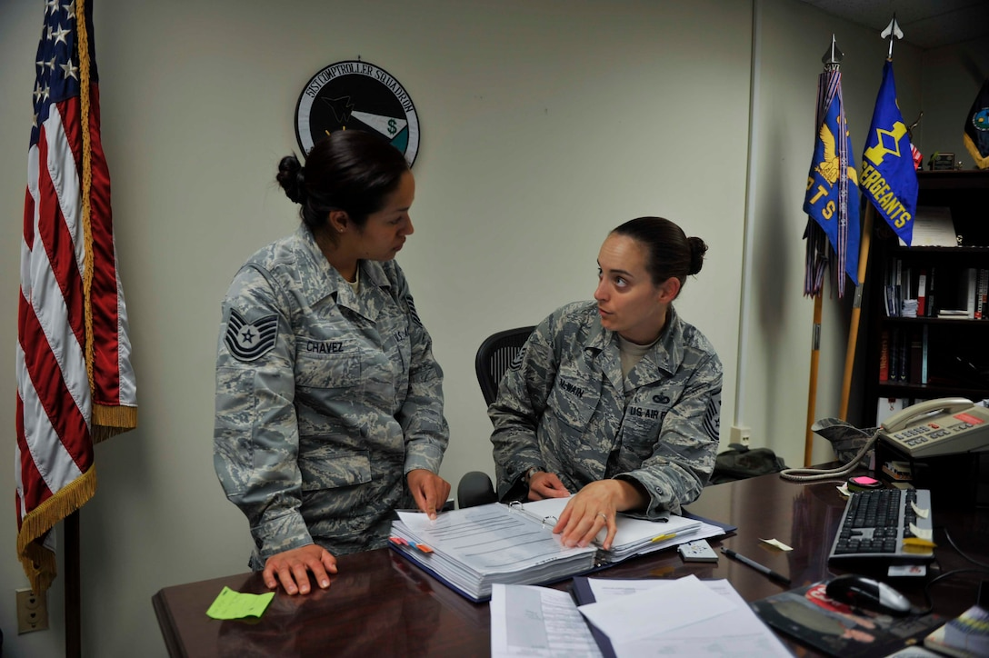 """Master Sgt. Jessica McWain, 51st Fighter Wing Staff Agencies and Comptroller Squadron first sergeant, explains the process of taking emergency leave to Tech. Sgt. Alejandra Chavez, 51st FW Equal Opportunity NCO in charge, during a """"Shadow the Shirt"""" day on Osan Air Base, Republic of Korea, Aug. 7, 2014. Six Airmen shadowed McWain during July and August to learn about a first sergeant's duties. (U.S. Air Force photo/Senior Airman David Owsianka)"""