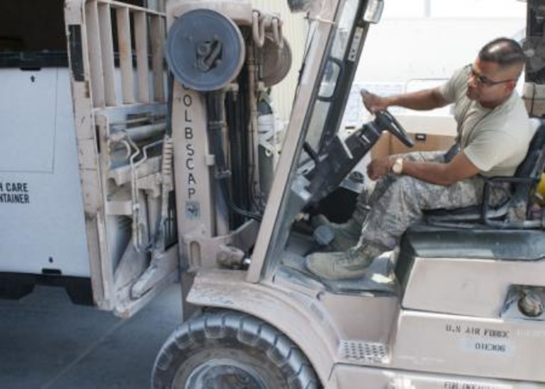 Tech. Sgt. Gautambhai Patel operates a forklift to help ready humanitarian aid pallets at a location in Southwest Asia Aug., 11, 2014. The pallets consist of food and water for humanitarian aid drops to assist displaced citizens in the vicinity of Sinjar, Iraq. (U.S. Air Force photo by Senior Airman Colin Cates)