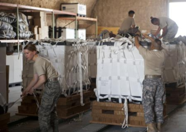 Service member volunteers push a completed pallet of food and water to prepare it for loading onto aircraft at a location in Southwest Asia Aug. 11, 2014. Volunteers from across the base came out to help build pallets of humanitarian aid. The pallets are being airdropped to displaced citizens in the vicinity of Sinjar, Iraq. (U.S. Air Force photo by Senior Airman Colin Cates)