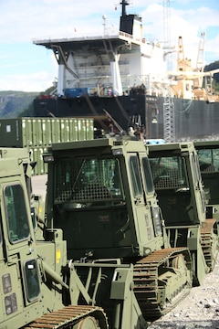 Military bulldozers and other equipment are staged for transportation at the designated offload pier during a pre-planned Single Ship Movement and offload of military equipment from a Maritime Prepositioning Force ship in the Trøndelag region of Norway.  U.S. Marines from 2nd Marine Logistics Group out of Camp Lejeune, NC, in coordination with their Norwegian counterparts, are modernizing some of the equipment currently stored within six caves as a part of the Marine Corps Prepositioning Program-Norway by placing approximately 350 containers of gear and nearly 400 pieces of heavy rolling stock into the storage caves.    Specific equipment which will greatly increase the program's readiness includes M1A1 Main Battle Tanks, Tank Retrievers, Armored Breeching Vehicles, Amphibious Assault Vehicles, Expanded Capacity Vehicle (ECV) Gun Trucks and several variants of the MTVR 7 ½ ton trucks.    Planning for this equipment refresh began in the spring of 2010.